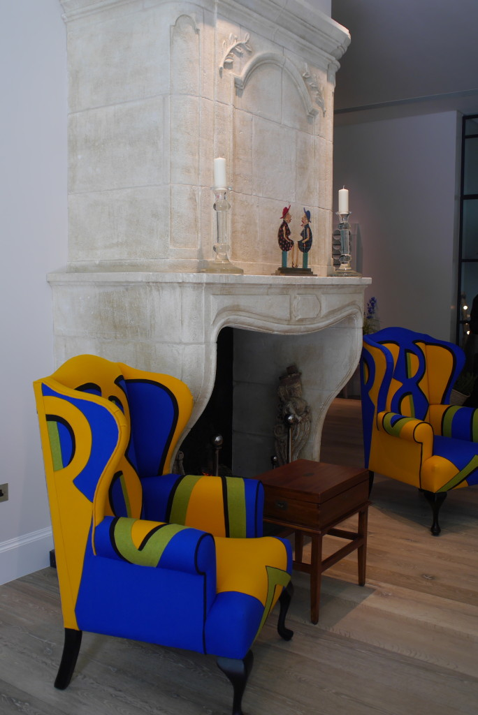 French stone fireplace alongside Kemp's vibrant designs